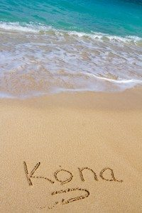 This vacation image shows the word Kona written in the sand with the Ocean water waves coming in to wash the writing away.